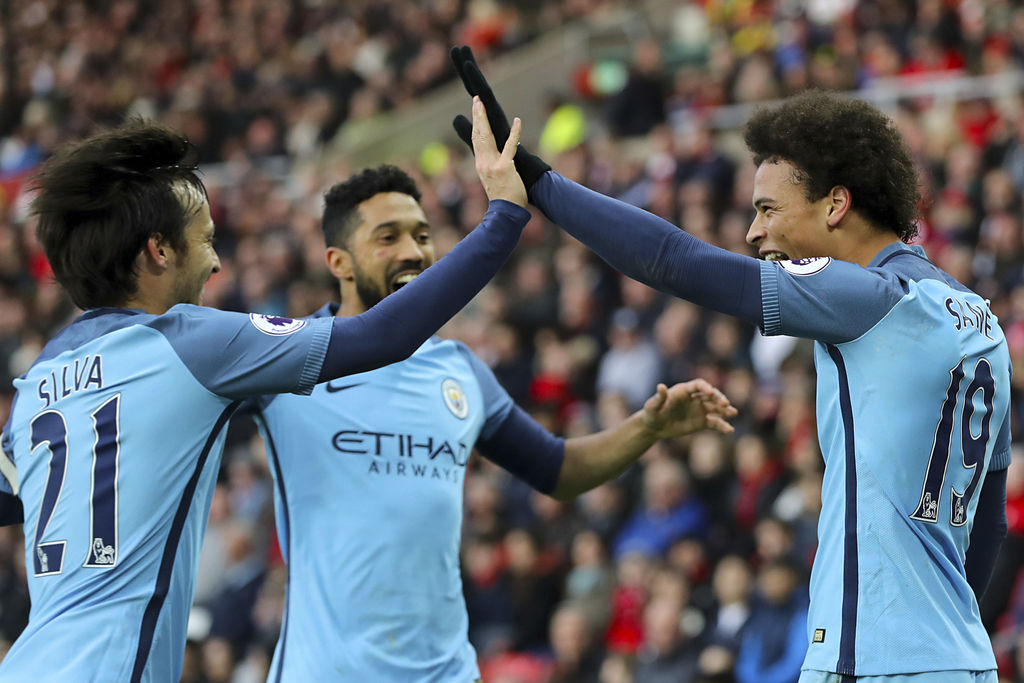 Manchester City's Leroy Sane, right, celebrates scoring his side's second goal of the game with team mates Manchester City's David Silv...