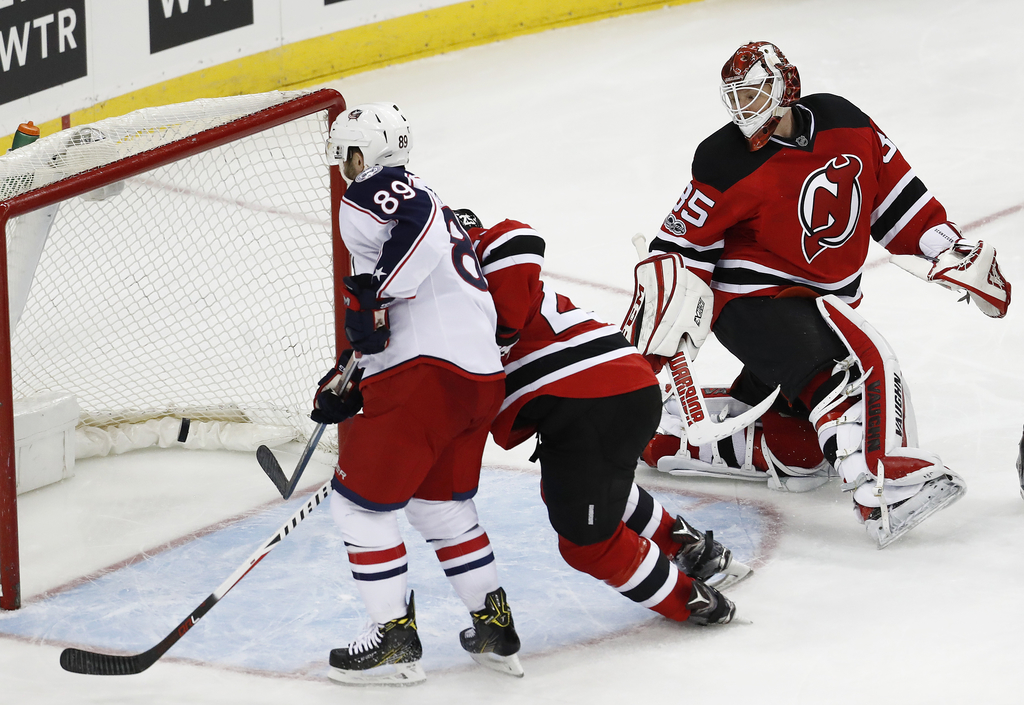 Columbus Blue Jackets center Sam Gagner, left, scores a goal on New Jersey Devils goalie Cory Schneider, right, during the third period...