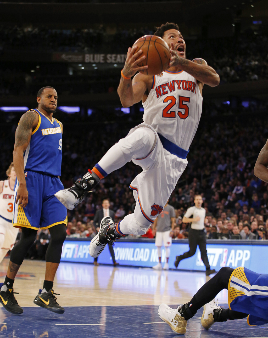 New York Knicks guard Derrick Rose (25) goes for a layup and knocks Golden State Warriors guard Stephen Curry to the floor as Warriors ...