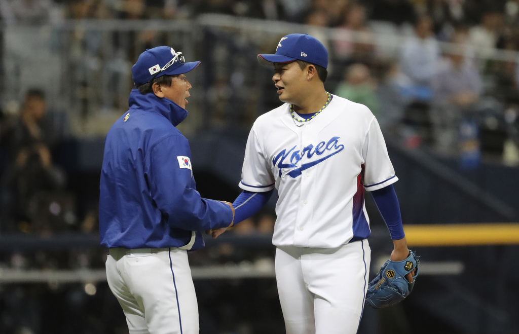 South Korea's pitching coach Son Dongyul, left, takes the ball from pitcher Sim Chang-min before leaving the mound during the sixth inn...