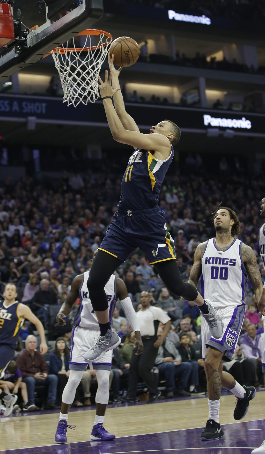 Utah Jazz guard Dante Exum, center, goes to the basket as Sacramento Kings' Ty Lawson, left, and Willie Cauley-Stein, right, look on du...