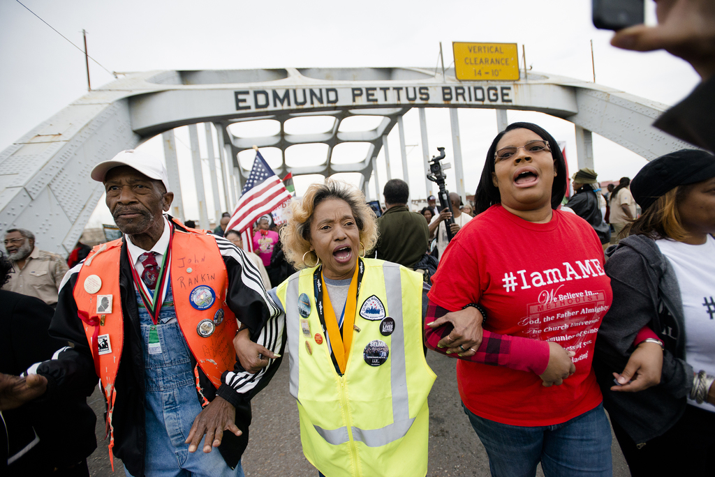 John Rankin, left, marches across the Edmund Pettus Bridge over the Alabama River in Selma, Ala., during the annual re-enactment of a k...