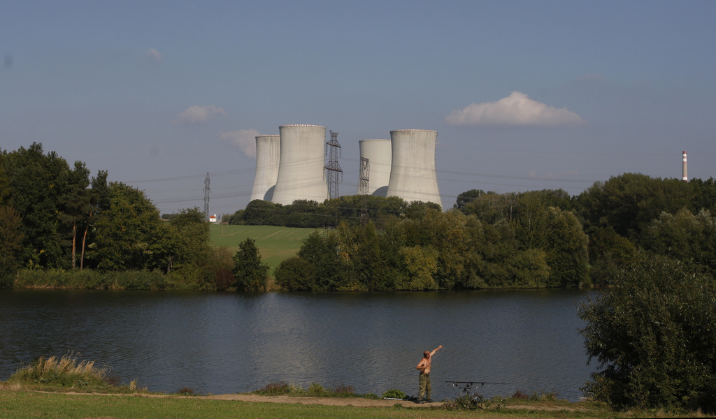 In this Sept.. 27, 2011, file photo,  a man fishes in a scene dominated by the towering Dukovany nuclear power plant in Dukovany, Czech...