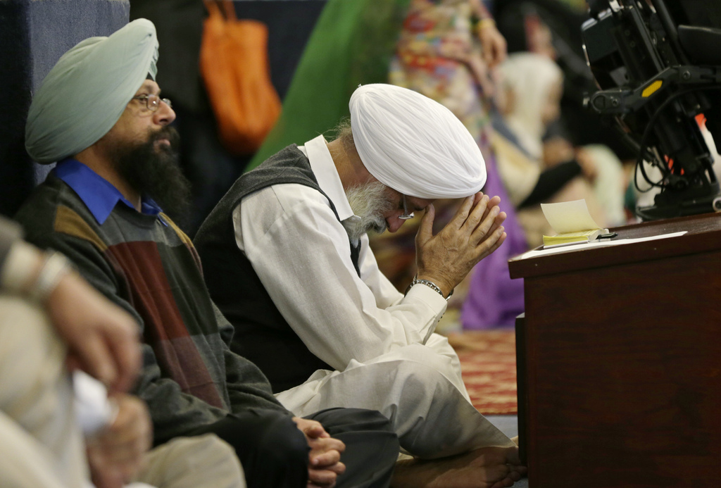 A man bows his head as he attends Sunday services at the Gurudwara Singh Sabha of Washington, a Sikh temple in Renton, Wash., Sunday, M...