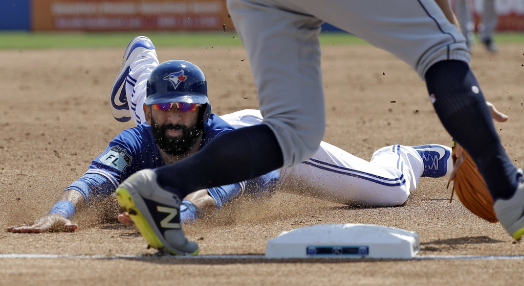 Toronto Blue Jays' Jose Bautista, left, slides into third base ahead of the tag by Tampa Bay Rays third baseman Evan Longoria with a st...