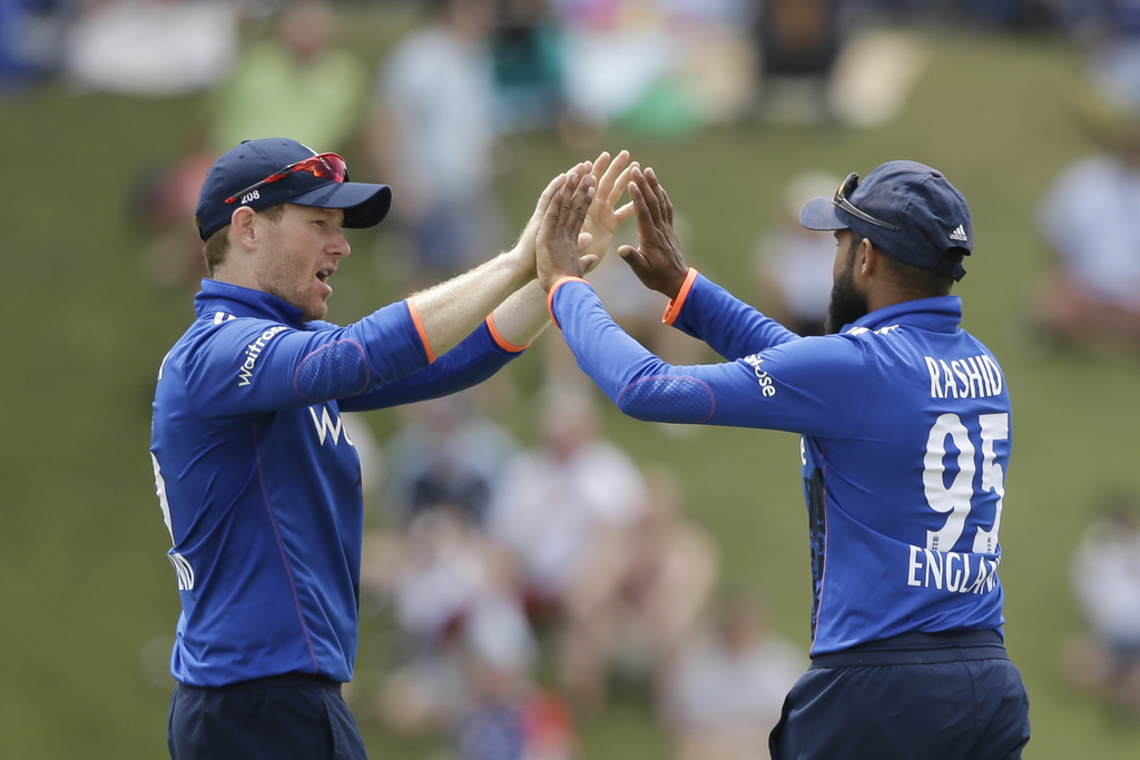 England's captain Eoin Morgan, left, congratulates bowler Adil Rashid after he caught West Indies' Jonathan Carter during their second ...