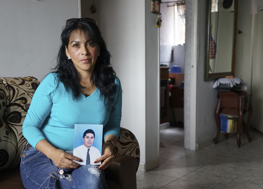 In this March 1, 2017 photo, Martha Antivar holds a portrait of her husband Oscar Hilarion in her mother-in-law's apartment in Bogota, ...