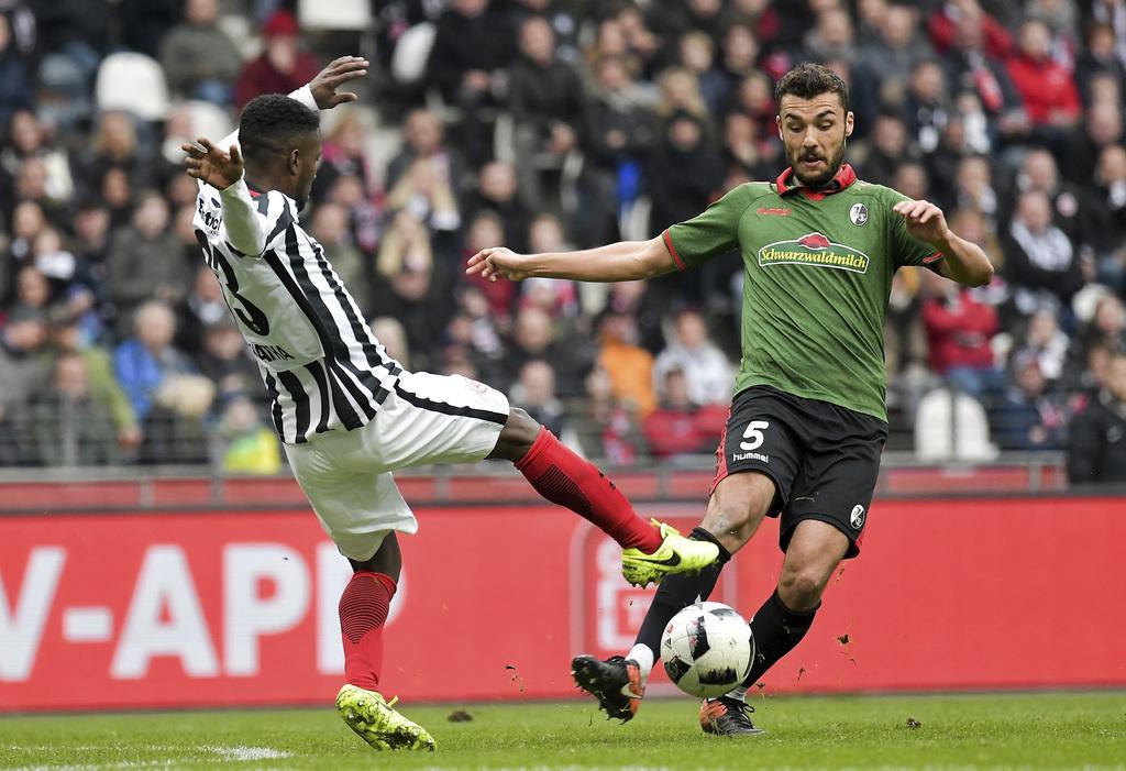 Frankfurt's Taleb Tawatha, left,  and Freiburg's Manuel Gulde challenge for the ball during the Bundesliga soccer match between Eintrac...