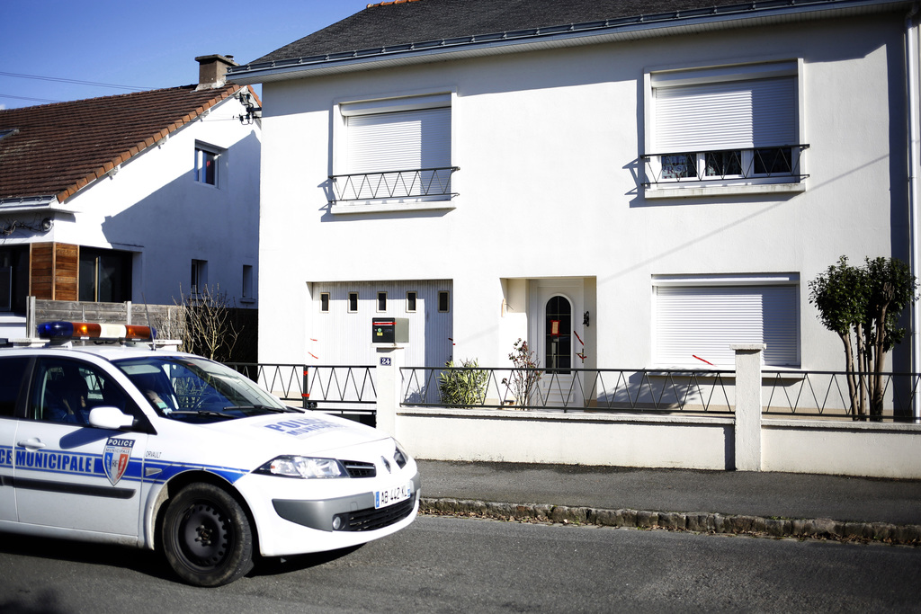 FILE - This Tuesday, Feb. 28, 2017 file photo shows a police car parked outside the house belonging to the missing Troadec family in Or...