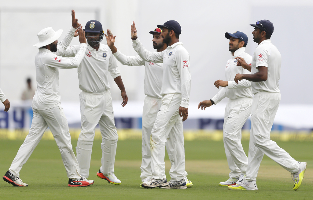 Indian players celebrate the dismissal of Australia's Mitchell Starc during the third day of their second test cricket match in Bangalo...