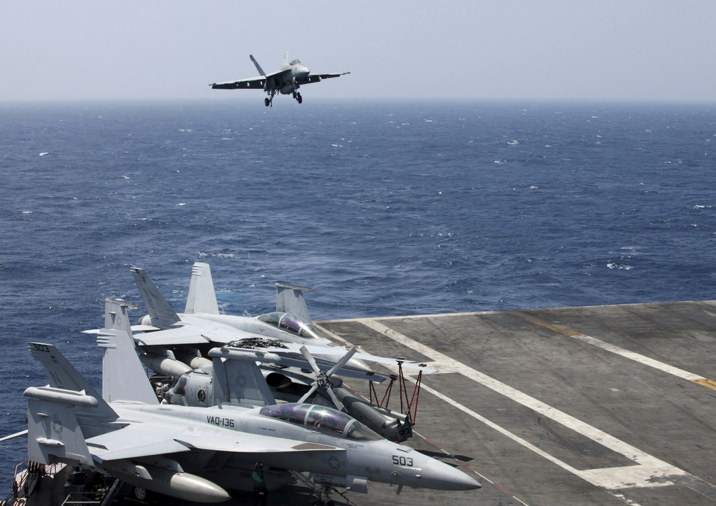 FILE - In this March 3, 2017 file photo, a U.S. Navy F18 fighter jet lands on the U.S. Navy aircraft carrier USS Carl Vinson (CVN 70) f...
