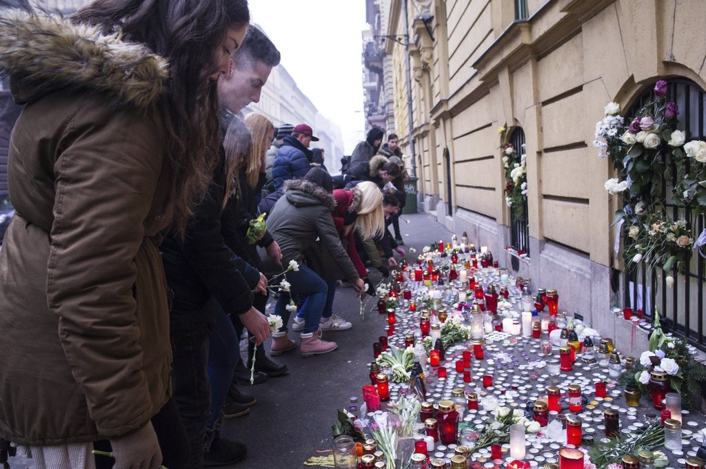 FILE - In this Jan. 23, 2017 file photo, Budapest students light candles and put flowers at a makeshift memorial outside Szinyei Merse ...