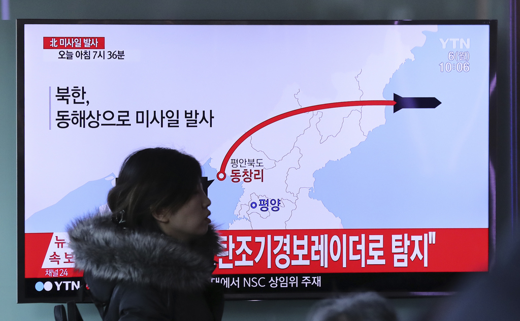 A visitor walks by the TV screen showing a news program reporting about North Korea's missile firing, at Seoul Train Station in Seoul, ...