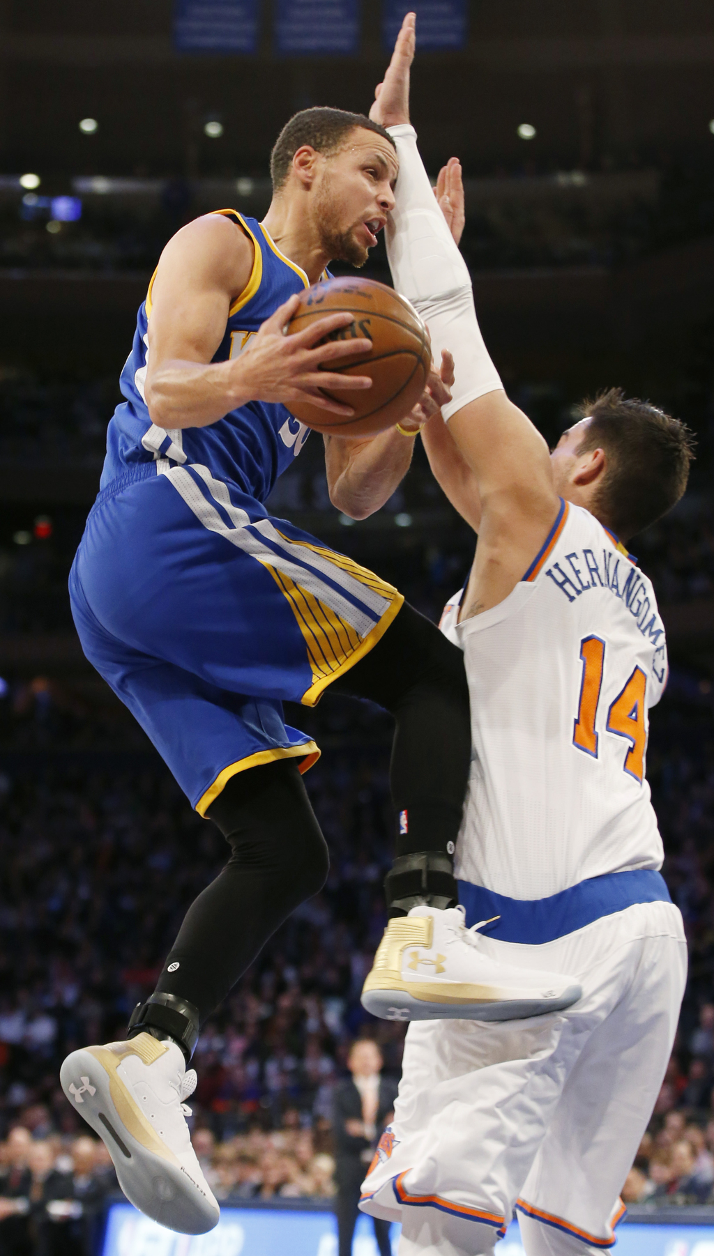 Golden State Warriors guard Stephen Curry, left, bumps into New York Knicks center Willy Hernangomez (14) as he goes up for a layup in ...