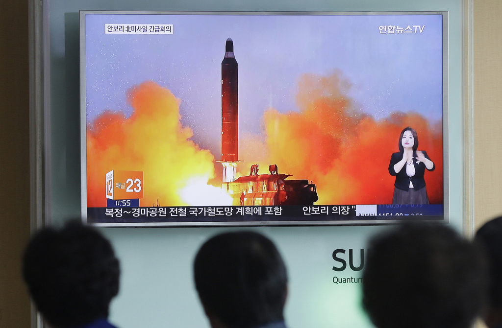 FILE - In this June 23, 2016, file photo, people watch a TV news channel airing an image of North Korea's ballistic missile launch publ...