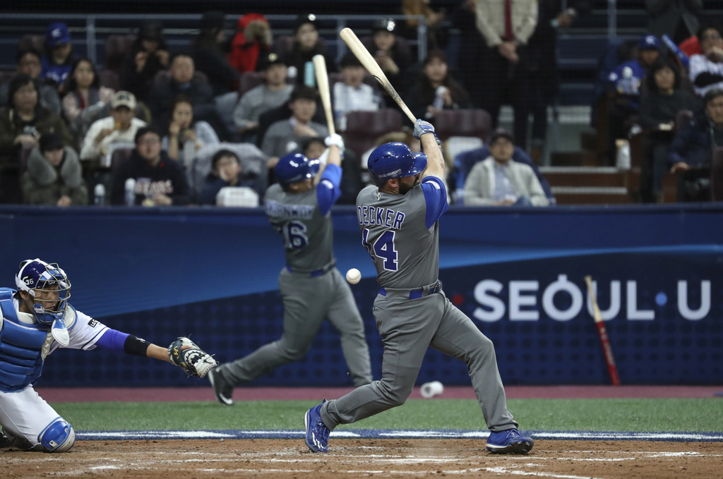 Israel's designated hitter Cody Decker, foreground, fouls off a pitch against South Korea during the fourth inning of their first round...