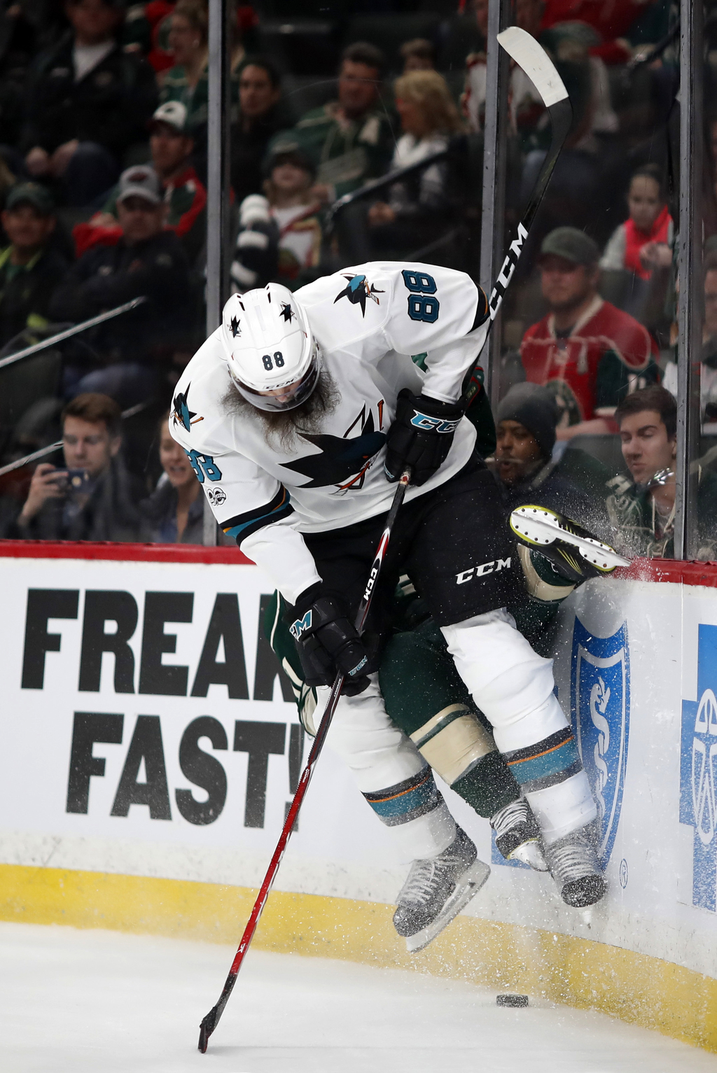 San Jose Sharks defenseman Brent Burns (88) checks Minnesota Wild left wing Zach Parise into the boards as they both pursue the puck in...