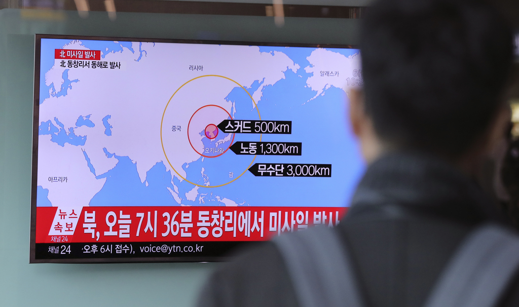 A man watches a TV news program reporting about North Korea's missile firing at Seoul Train Station in Seoul, South Korea, Monday, Marc...