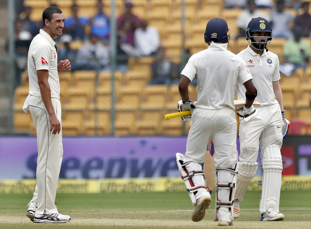 Australia's Mitchell Starc, left, smiles at India's Abhinav Mukund, center, after a six was hit on his delivery during the third day of...