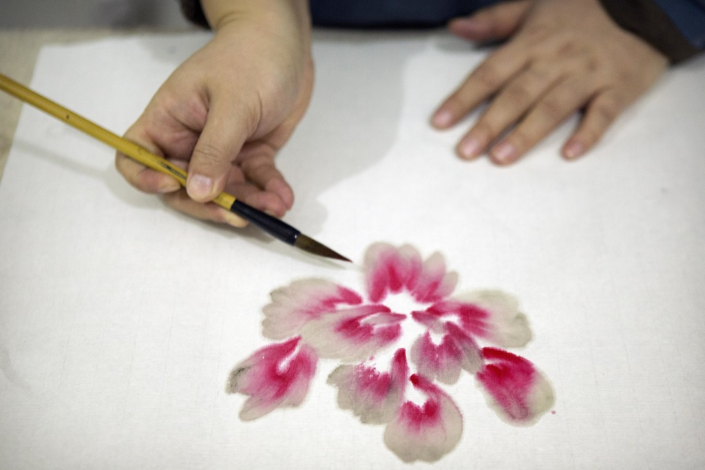 In this Monday, Feb. 27, 2017 photo, Ye Haiyan paints a watercolor painting in her studio on the outskirts of Beijing. Ye has resorted