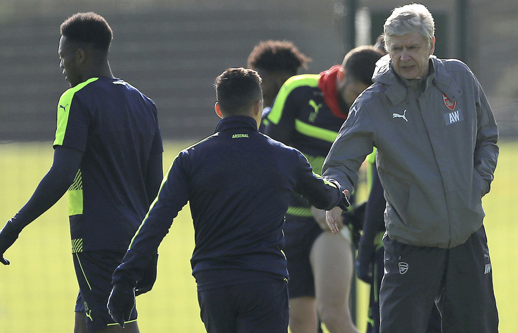 Arsenal's Alexis Sanchez, left, shakes hands with manager Arsene Wenger during a training session at the Arsenal Training Centre, Londo...