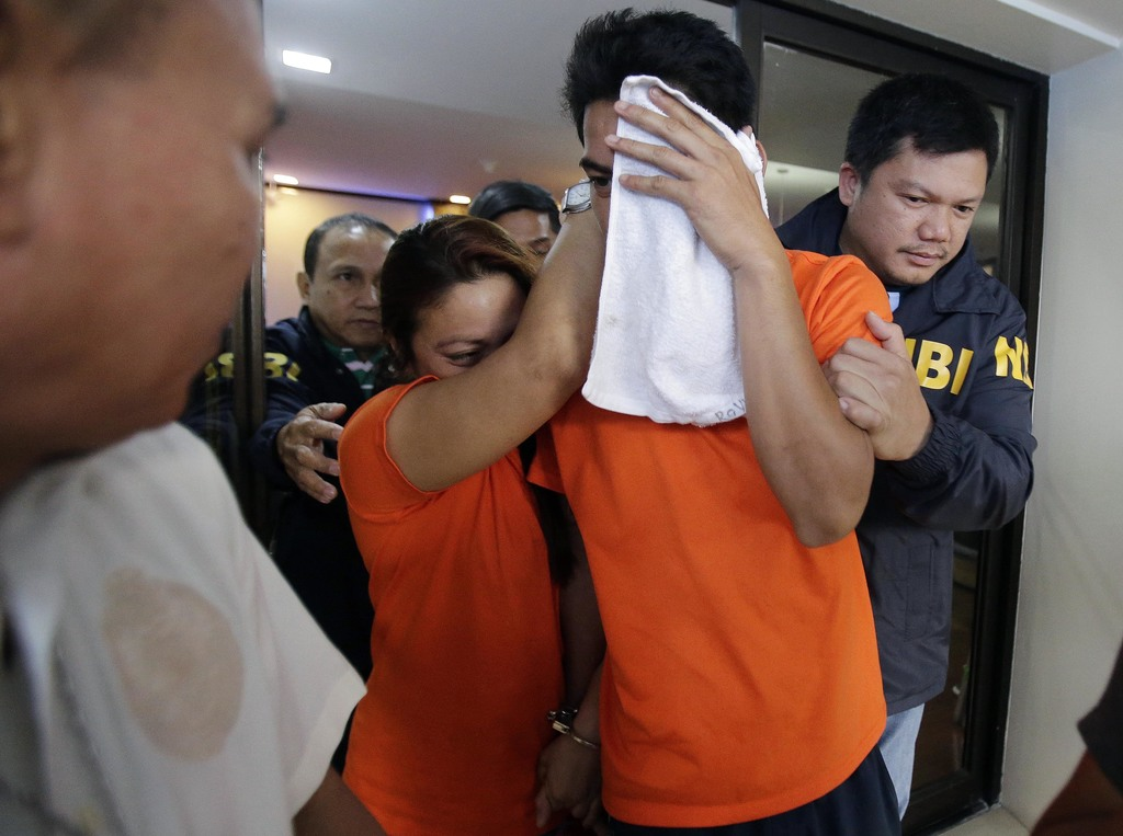 FILE - In this April 26, 2016 file photo, suspects accused of involvement in child trafficking and pornography are escorted by agents o...