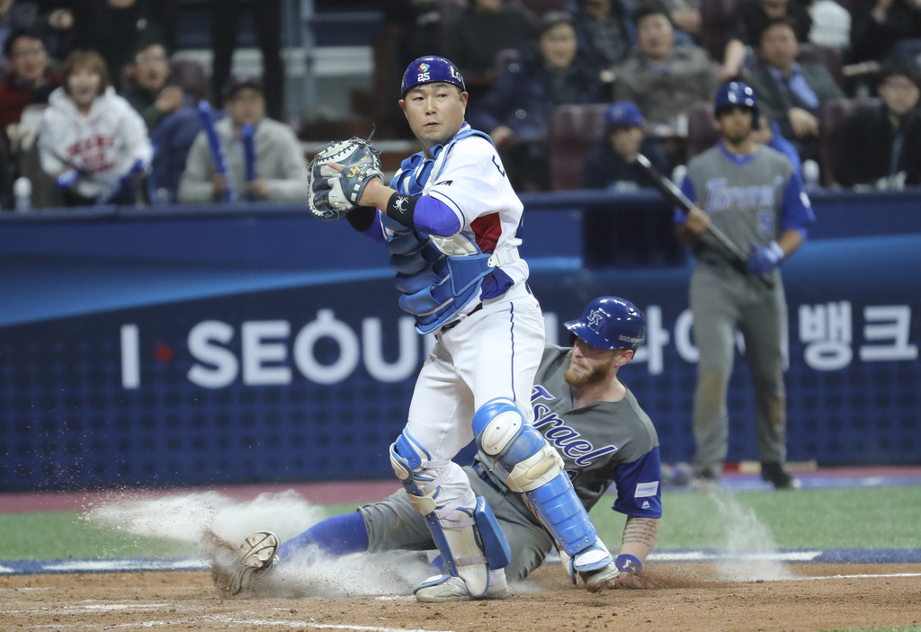 Israel's Zach Borenstein is forced out at home as South Korea's catcher Yang Eui-ji tries to throw to first during the eighth inning of...