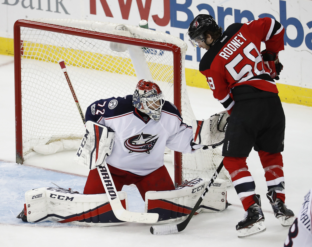Columbus Blue Jackets goalie Sergei Bobrovsky, of Russia, left, tries to glove the puck as New Jersey Devils center Kevin Rooney (58) a...