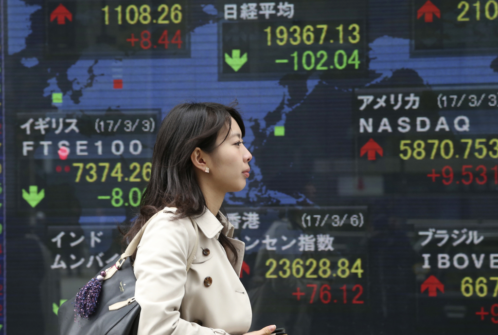 A woman walks by an electronic stock board of a securities firm in Tokyo, Monday, March 6, 2017. Shares were mixed in Asia early Monday...