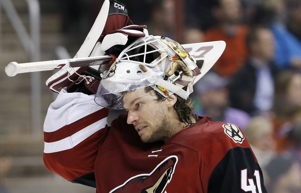 This March 22, 2016 photo shows Arizona Coyotes' Mike Smith putting his mask back on as he skates back to his position during the first...