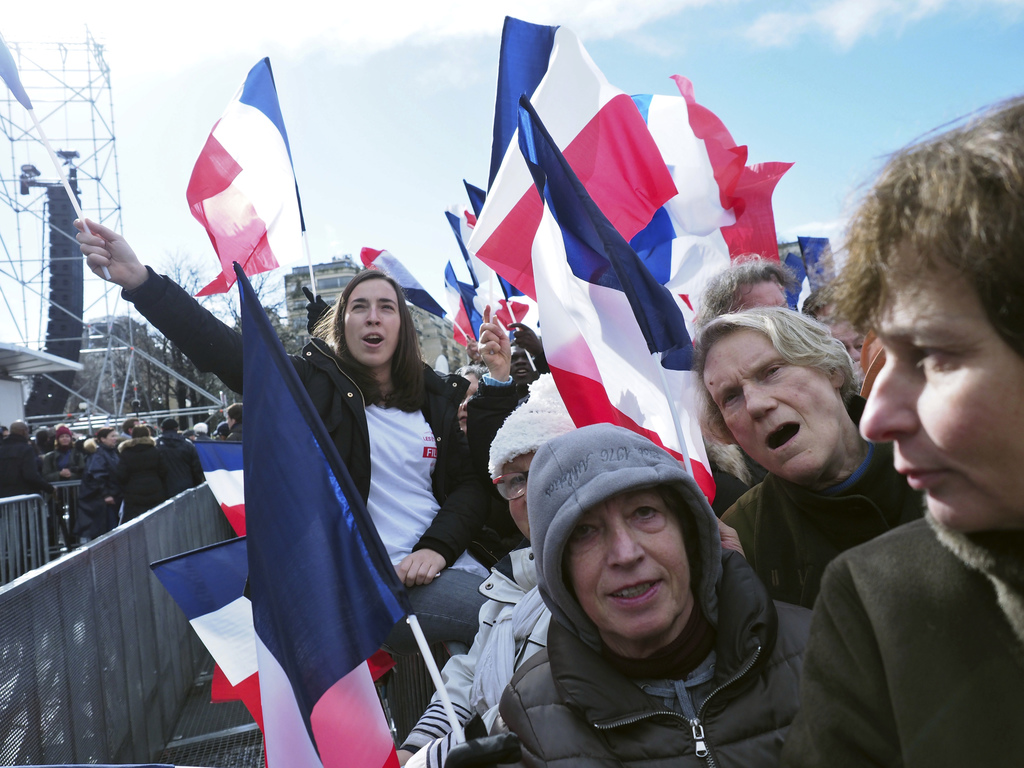Supporters of conservative presidential candidate Francois Fillon waves French flag, during a rally in Paris, Sunday, March 5, 2017. Th...