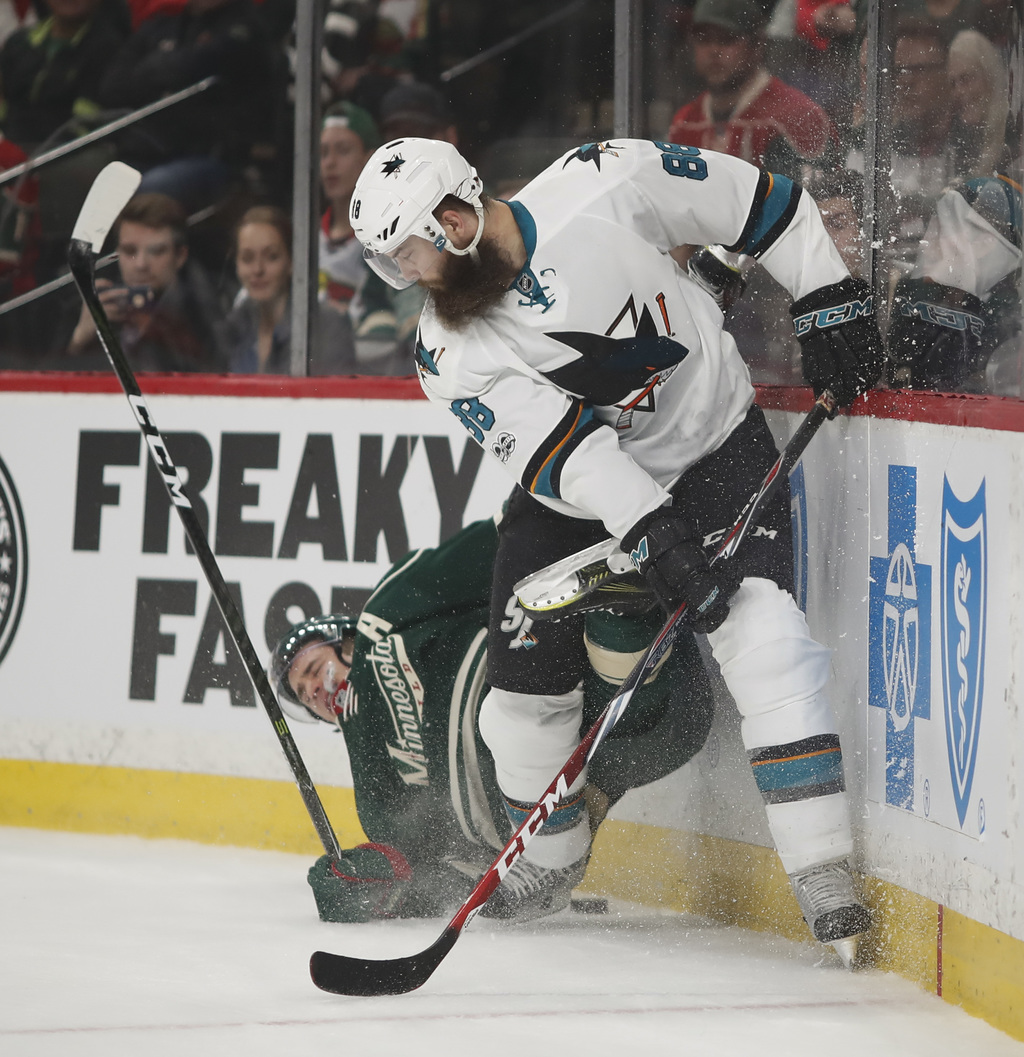 San Jose Sharks defenseman Brent Burns (88) checks Minnesota Wild left wing Zach Parise (11) in the boards as they both pursued a puck ...