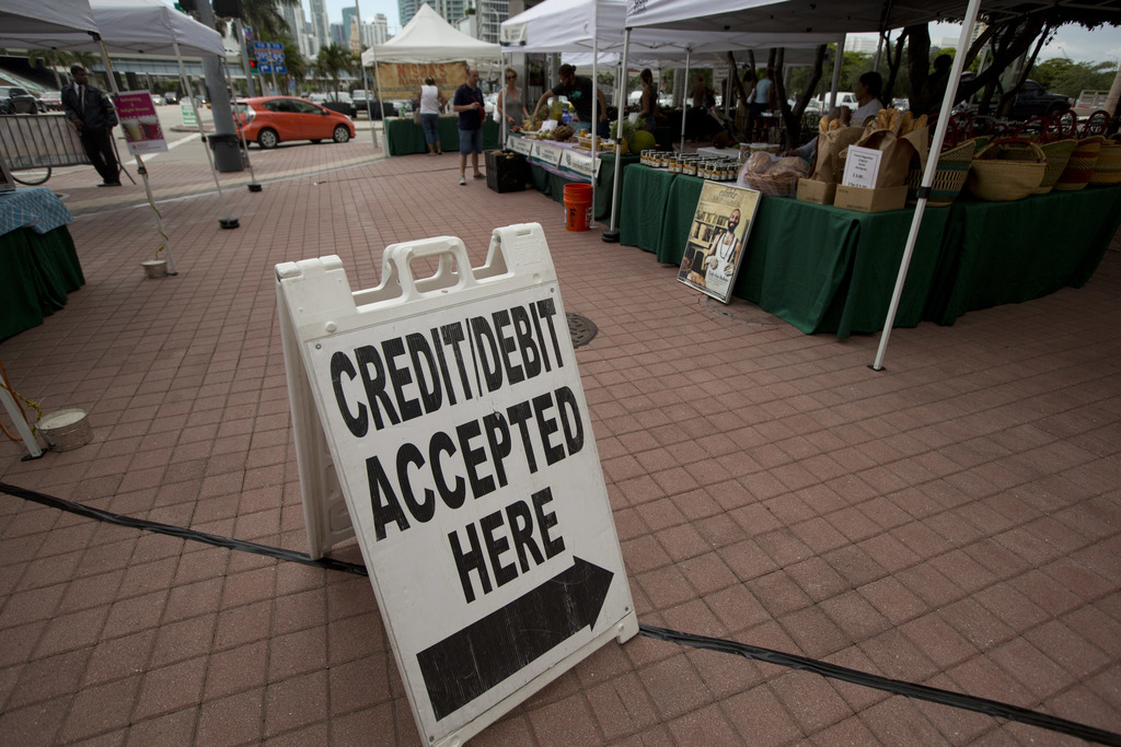 FILE - In this June 8, 2015, file photo, credit card customers are directed to a pay station at the green market in downtown Miami. On ...