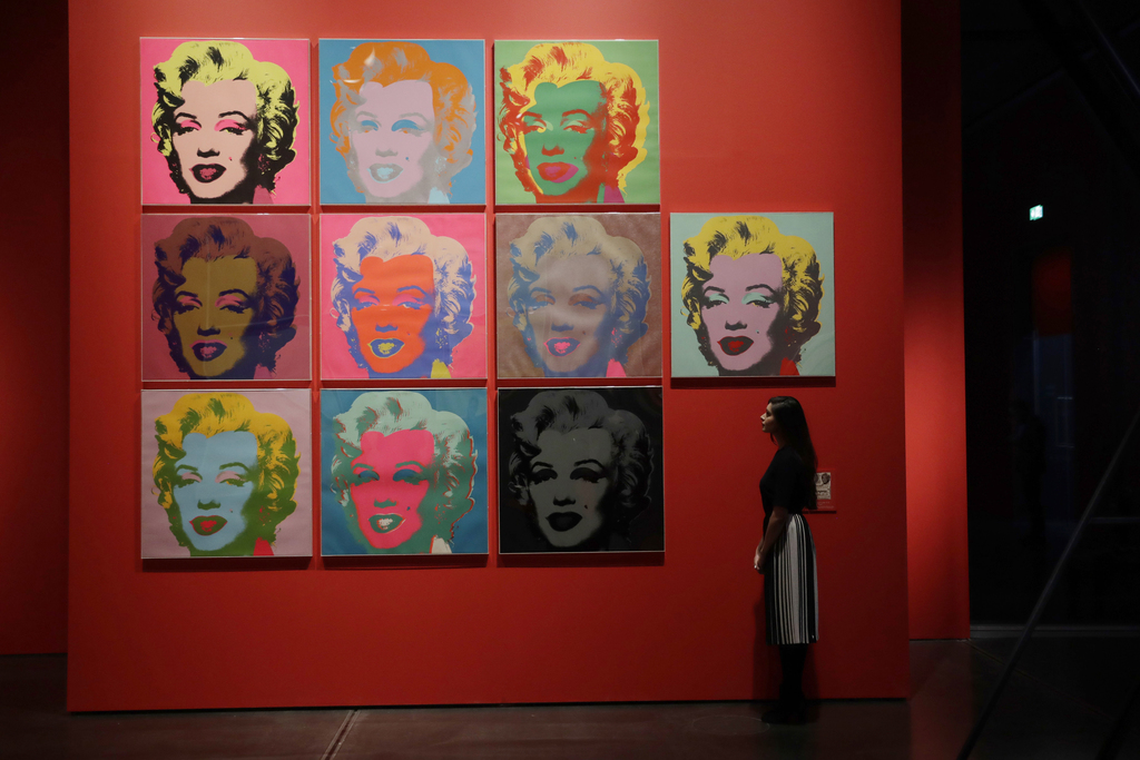 """A British Museum representative poses for photographs next to Andy Warhol's """"Marilyn 1967, 10 Color Screenprints"""" which feature in """"The..."""