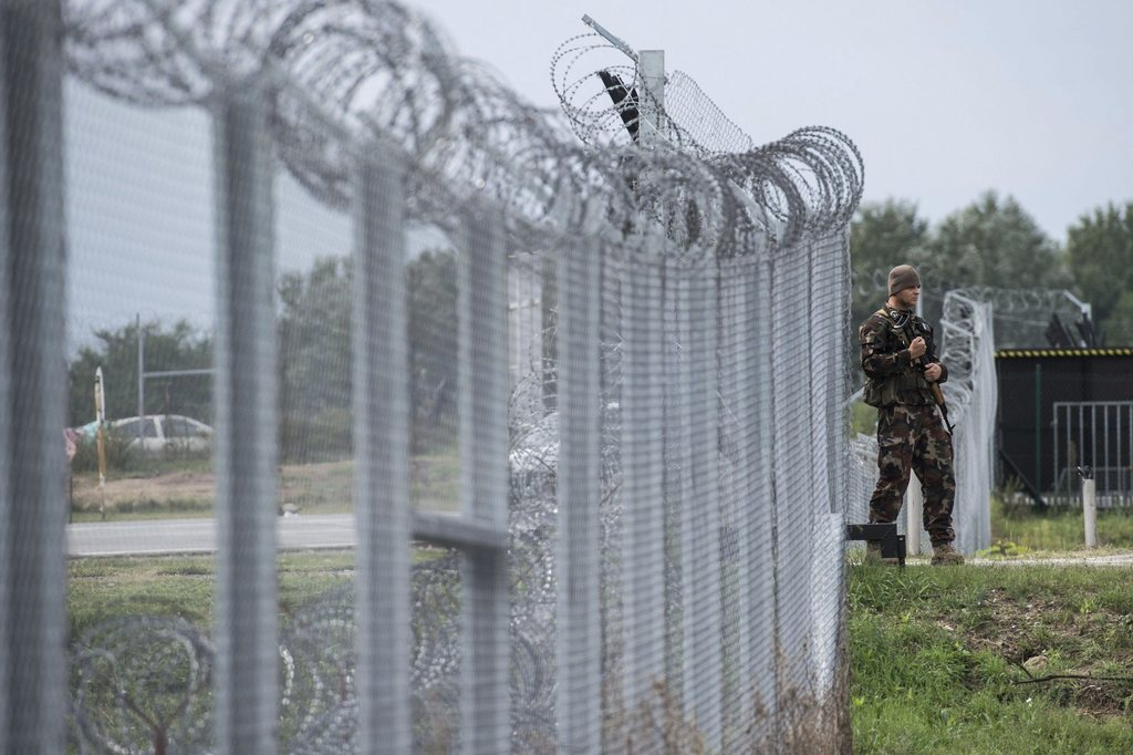 FILE - In this Sept. 21, 2016 file photo a Hungarian soldier patrols at the transit zone at Hungary's southern border with Serbia near ...