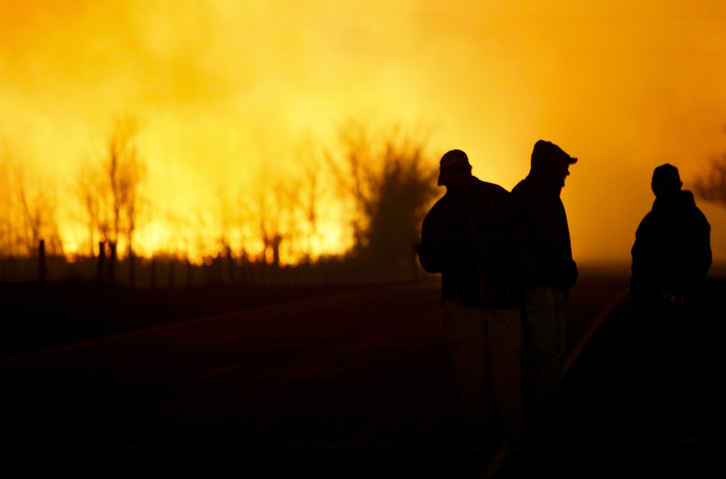 People are silhouetted against the orange glow of the fire as they watch a large grass fire burning out of control on Monday, March 6, ...