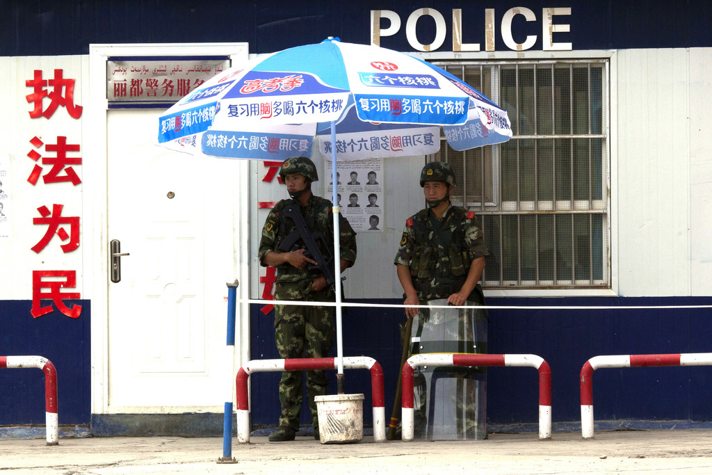 FILE - In this July 17, 2014 file photo, armed Chinese paramilitary policemen stand on duty near wanted posters at a check point in Aks...