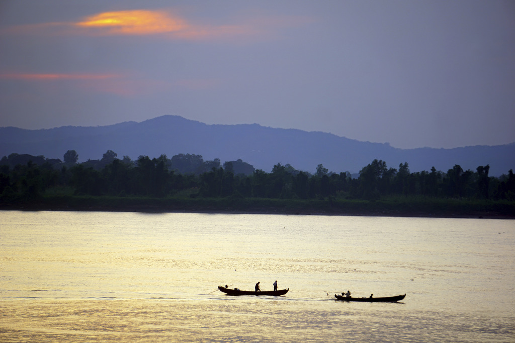 In this Jan. 23, 2017 photo, the last of the day's fishing boats ply the Salween River which flows by Mawlamyine to the Gulf of Martaba...