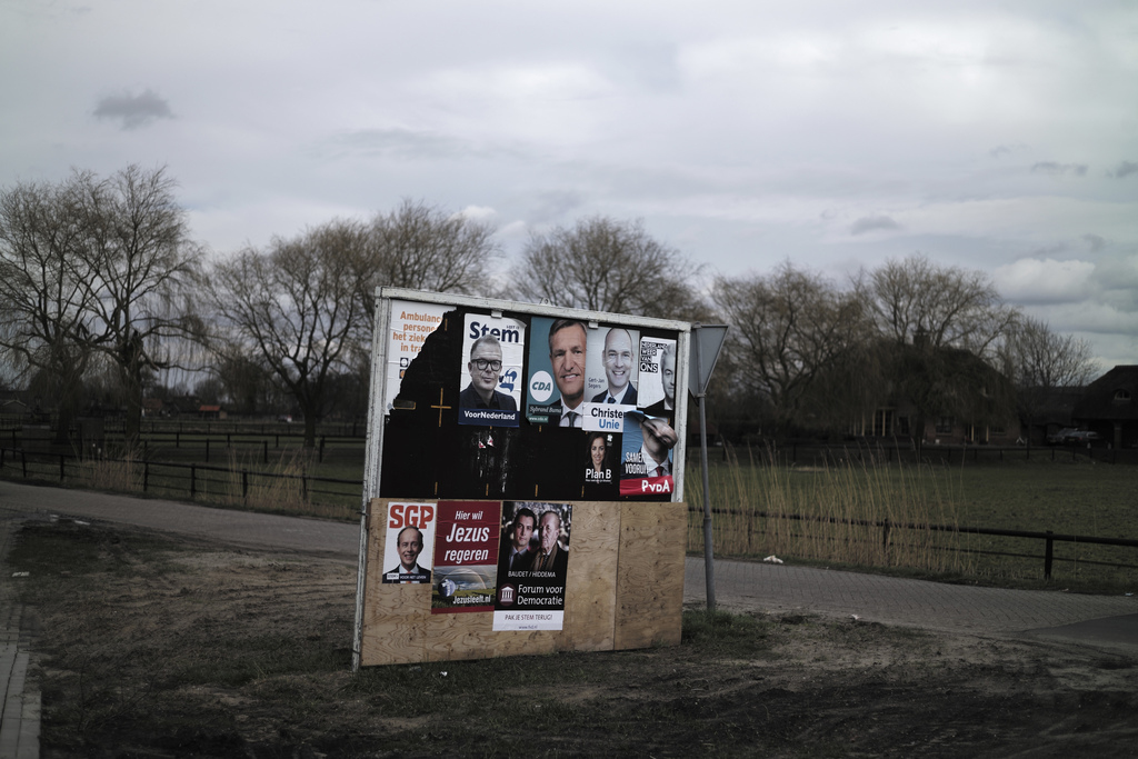 In this Saturday, March 4, 2017 photo, an election billboard with posters of various political parties is displayed in a street median ...