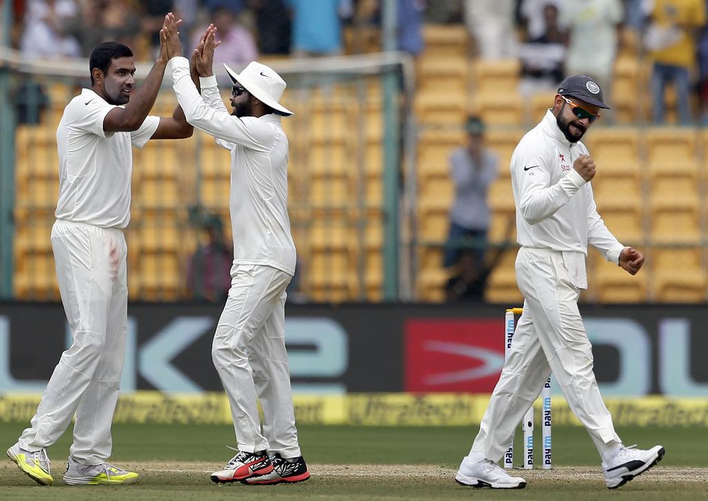 India's captain Virat Kohli, right, and teammates Ravichandran Ashwin, left, and Ravindra Jadeja celebrate the dismissal of Australia's...