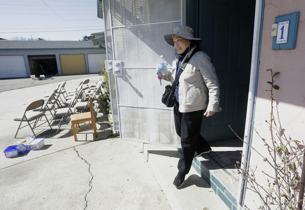 In this March 1, 2017 photo, displaced resident Hien Nguyen exits the home of her grandson who has also been displaced for flood damage...