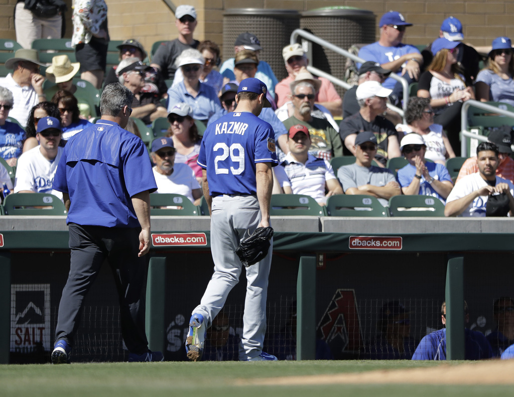 Los Angeles Dodgers' Scott Kazmir leaves with a trainer during the second inning of a spring training baseball game against the Colorad...