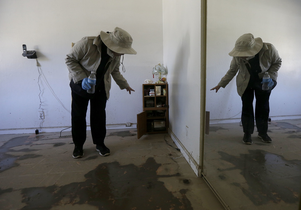 In this March 1, 2017 photo, displaced resident Hien Nguyen gestures toward flood damage in her home while interviewed in San Jose, Cal...