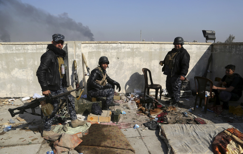 Soldiers take combat positions as Iraqi security forces advance during fighting against Islamic State militants in western Mosul, Iraq,...