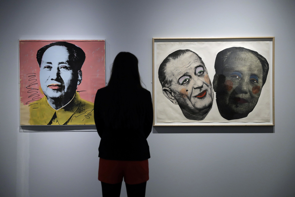 """A British Museum representative poses for photographs next to Andy Warhol's """"Mao"""", left, and Jim Dine's """"Drag: Johnson and Mao"""" which f..."""