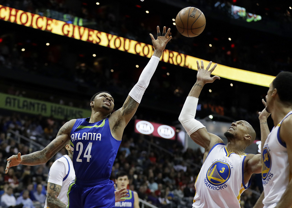 Atlanta Hawks' Kent Bazemore, left, reaches for a ball against Golden State Warriors' David West in the second quarter of an NBA basket...