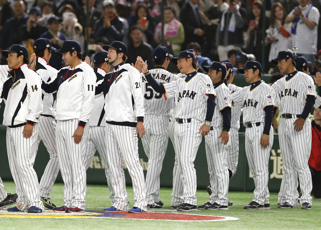 Japan's manager Hiroki Kokubo, fourth from right, celebrates with his players after beating Cuba 11-6 in their first round game of the ...