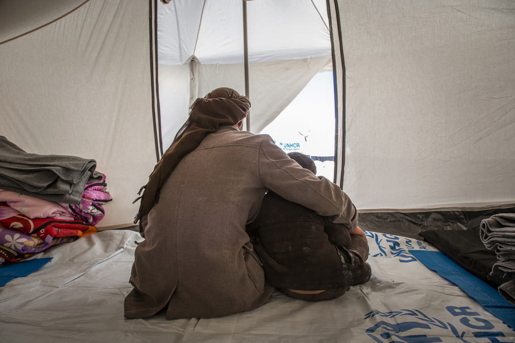 In this picture taken, Feb. 16, 2017, an Iraqi father, who fled violence in Mosul with his family, sits with his children in their tent...