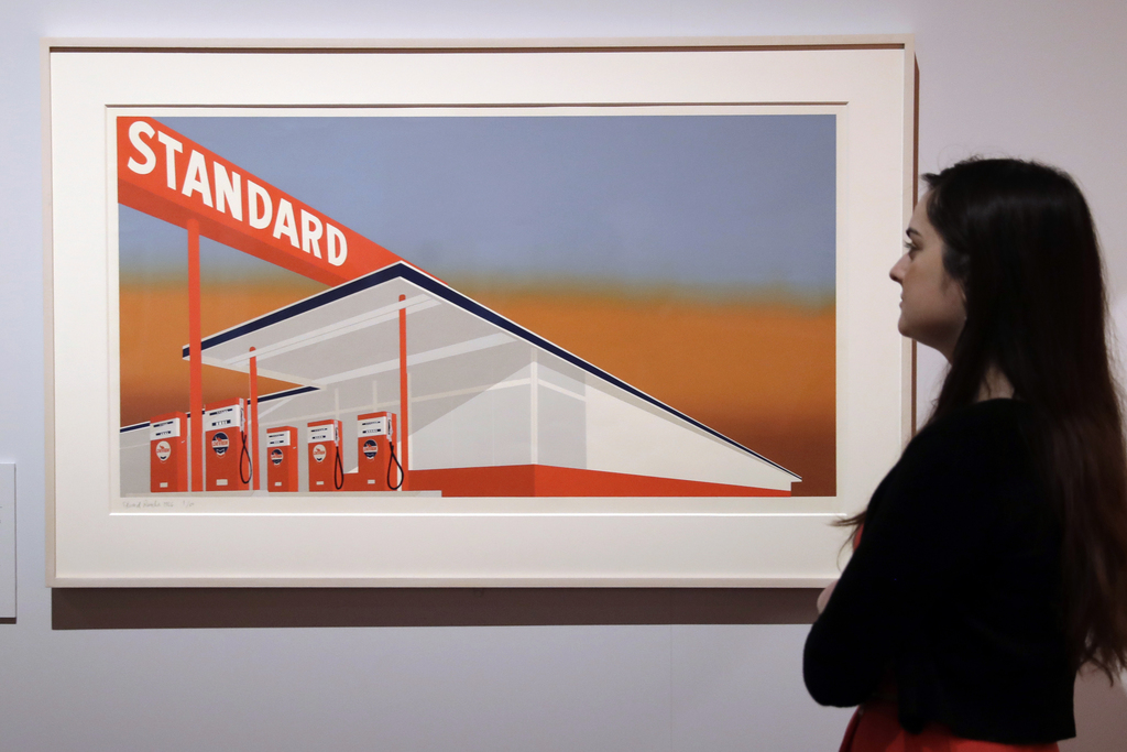 """A British Museum representative poses for photographs next to """"Standard Station"""" by Edward Ruscha which features in """"The American Dream..."""