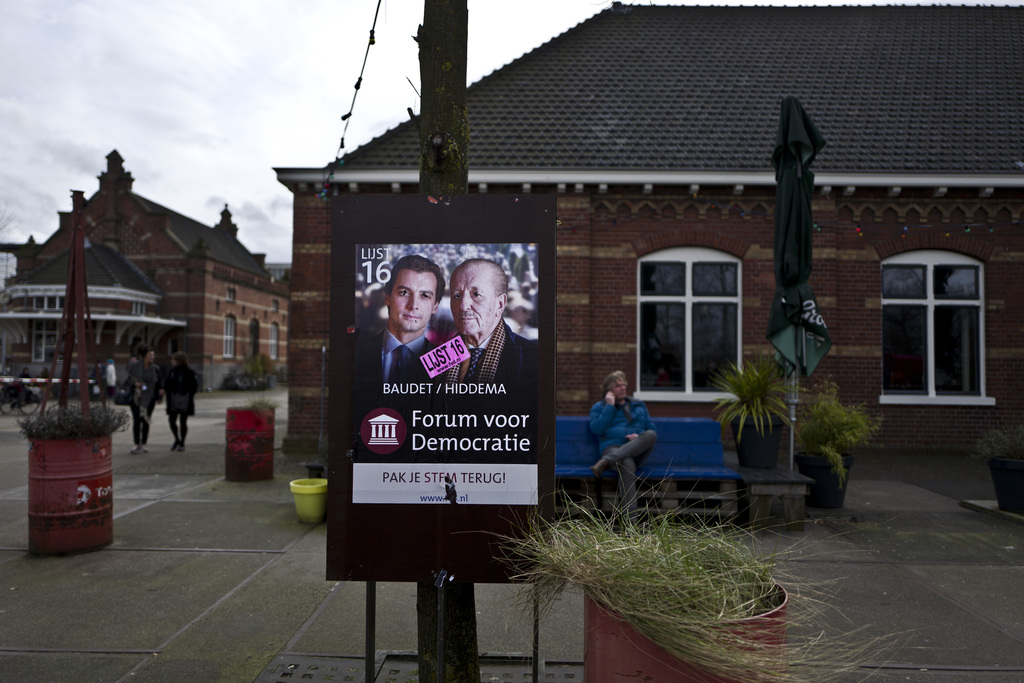 In this Sunday, March 5, 2017 photo, a damaged election poster showing, left, Thierry Baudet and Theo Hiddema, from the Forum for Democ...